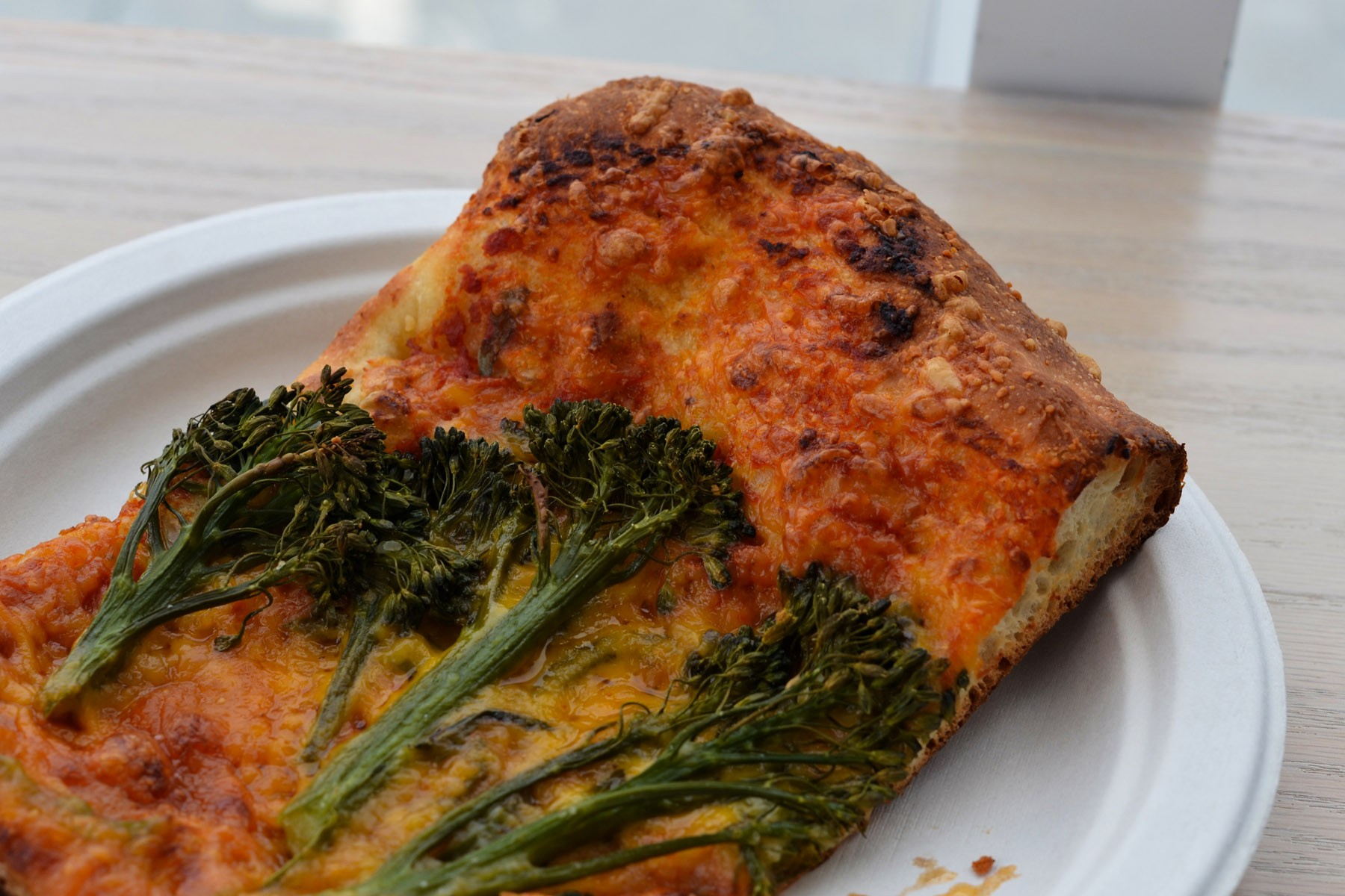 A big fat slice of vegetarian pizza, served on a compostable plate.