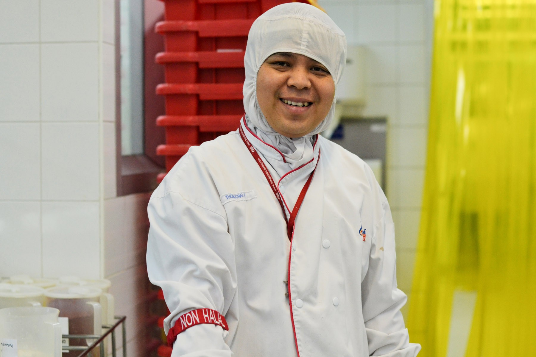 An employee presents his non halal arm band, one way the factory makes sure all halal foods are handled properly. -1
