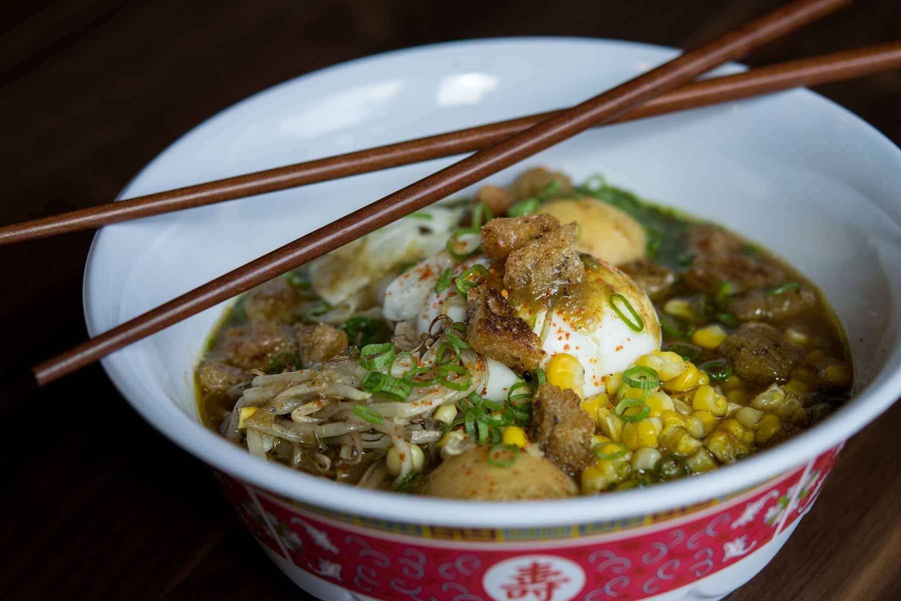 Matzo ball ramen with chicken broth, burnt onion, schmaltz tare, corn, and spicy chicken at Little Donkey. Photo by Andrea Merrill.