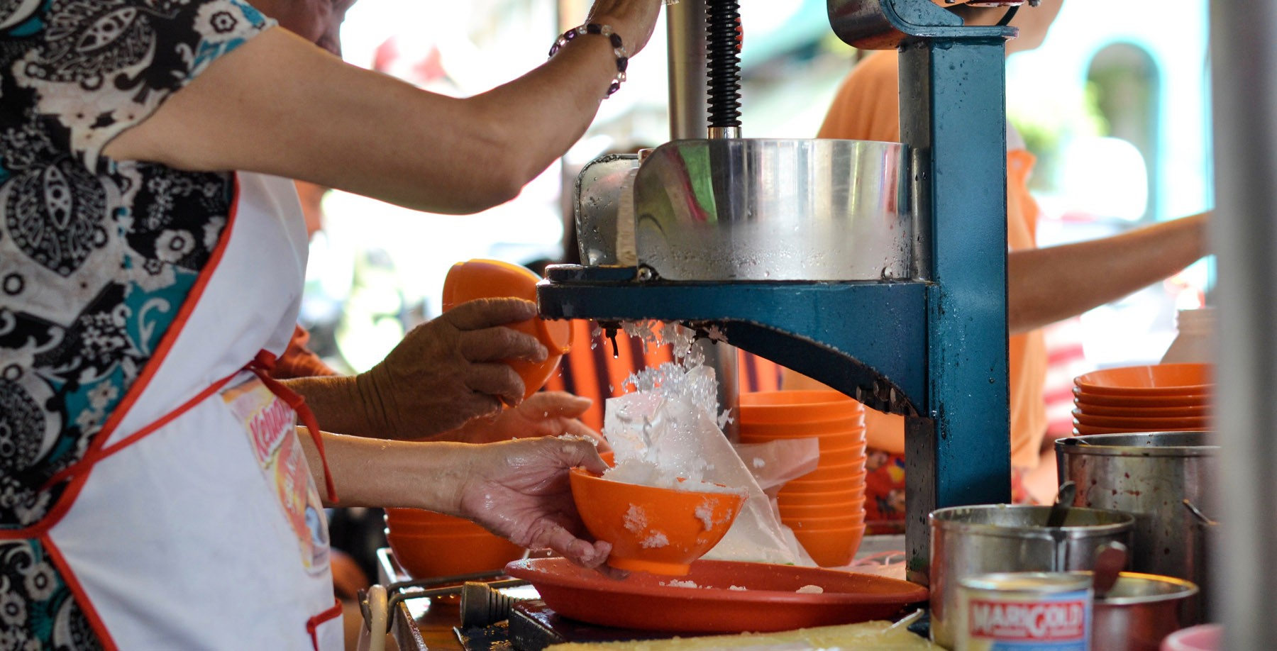 Ice blocks get shaved by a hand cranked machine.