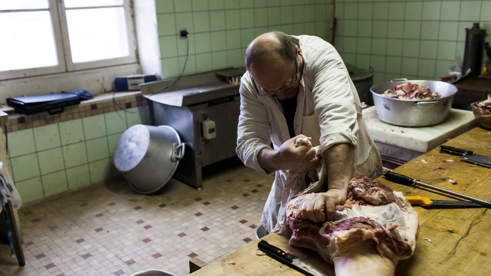 15/01/2014 - France / Aquitaine - La decoupe de la carcasse est une affaire de specialiste. ici le boucher desosse le futur jambon qui ira rejoindre le sechoir pendant plusieurs mois. Le tue-cochon, ou fete du cochon, est une tradition des campagnes francaises, qui correspond a l'abattage, la decoupe et la cuisine de la viande de porc. Autrefois moment important de la vie rural, cette tradition se perd aujourd'hui. Simon Lambert / Haytham Pictures 15/01/2014 - France / Aquitaine - Kill the pig - Slicing the carcass is alo a matter of specialist. The butcher here prepares the ham before it will be dried several months. Simon Lambert / Haytham Pictures