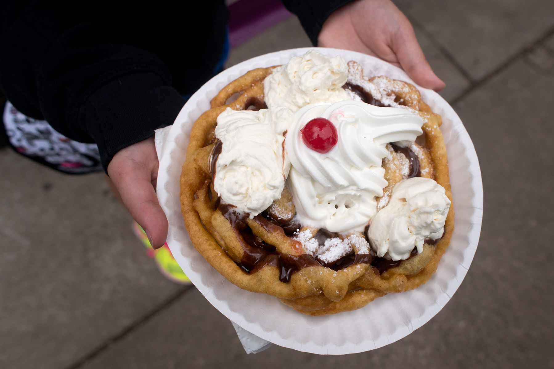 The Funnel Cake booth at the Minnesota State Fair serves a variety of funnel cakes including this sundae version with ice cream and chocolate sauce.