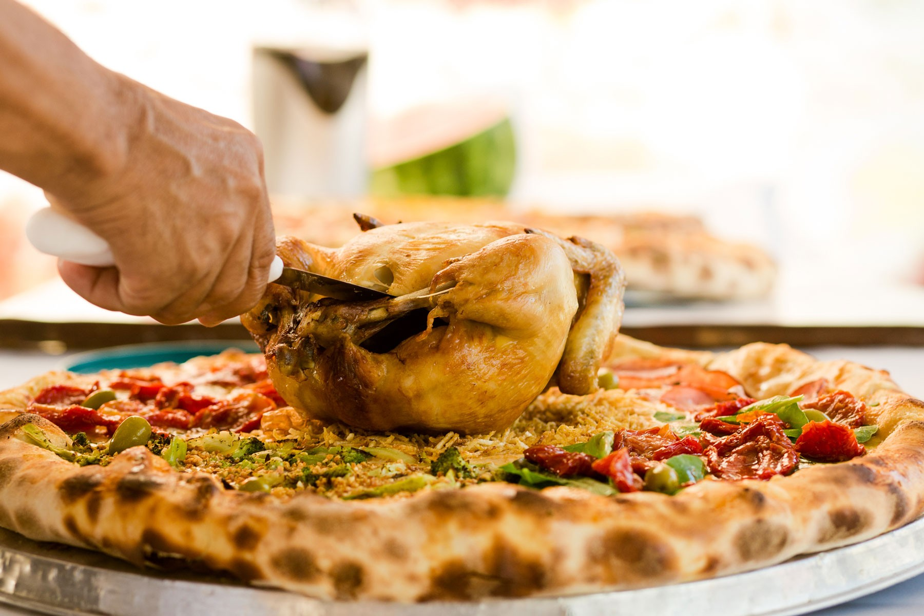 cutting-through-roasted-chicken-on-batepapo-pizza