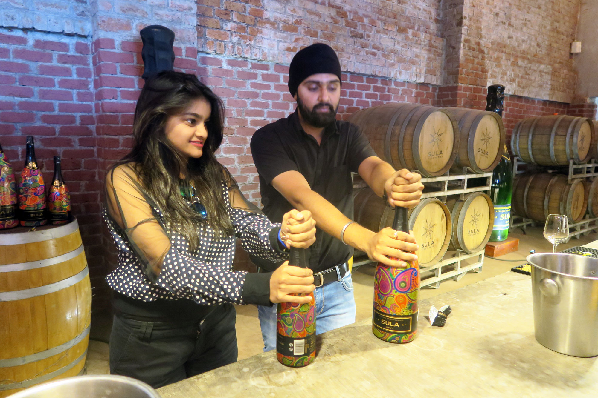 indian-vineyard-Indor-Surname-shows-Kritika-Patel-how-to-open-a-bottle-of-sparkling-wine