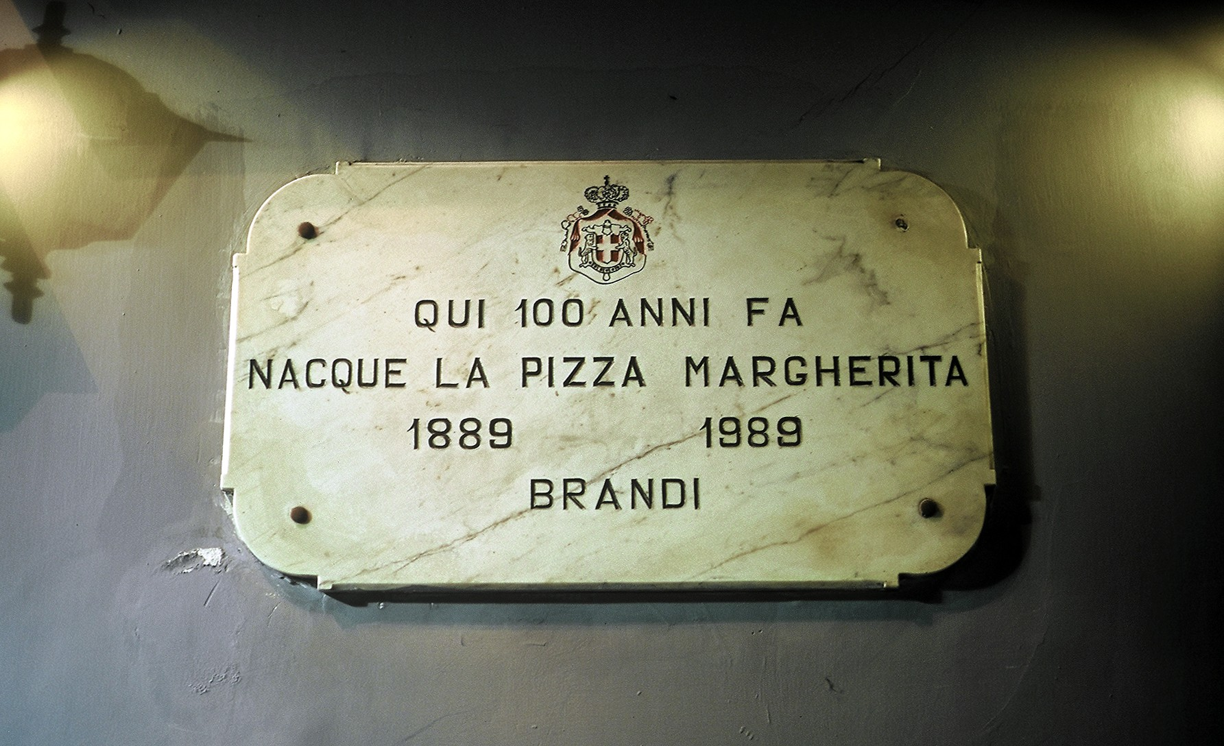 A marble plaque on the side of Pizzeria Brandi marking their 100th anniversary.