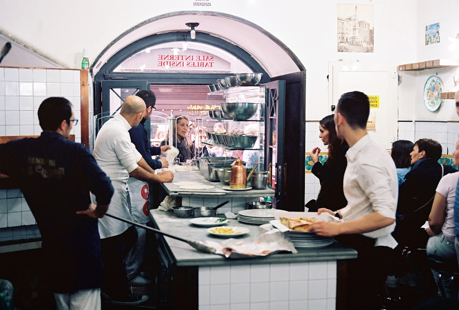 Patrons chat with the pizzaioli at Lombardi a Santa Chiara while they wait for their