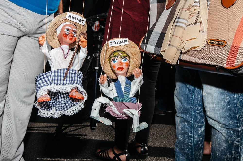Protestors fight marionette dolls while waiting for tacos during a protest by the Culinary Union which built a