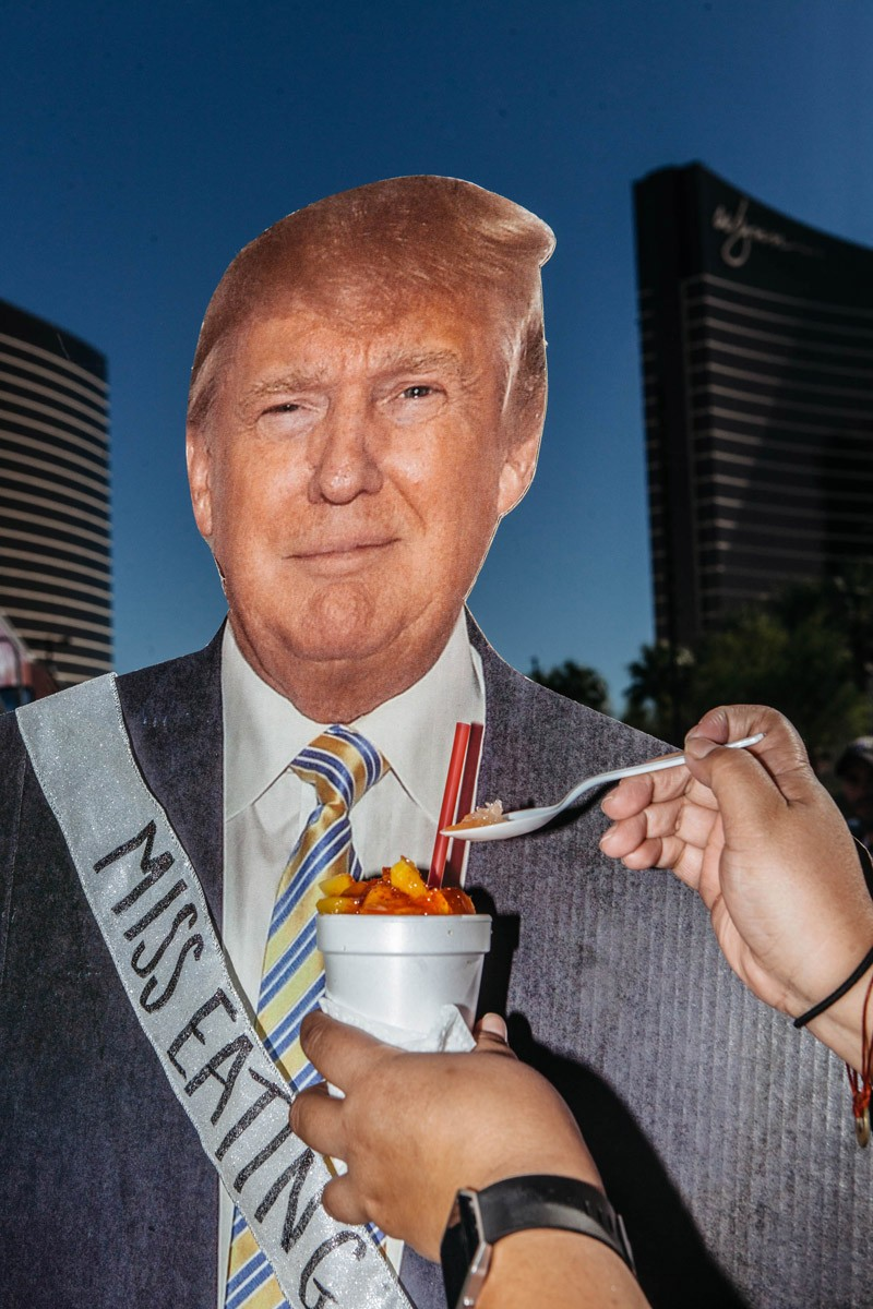 A protestor feeds a Trump cutout a fruit raspada.